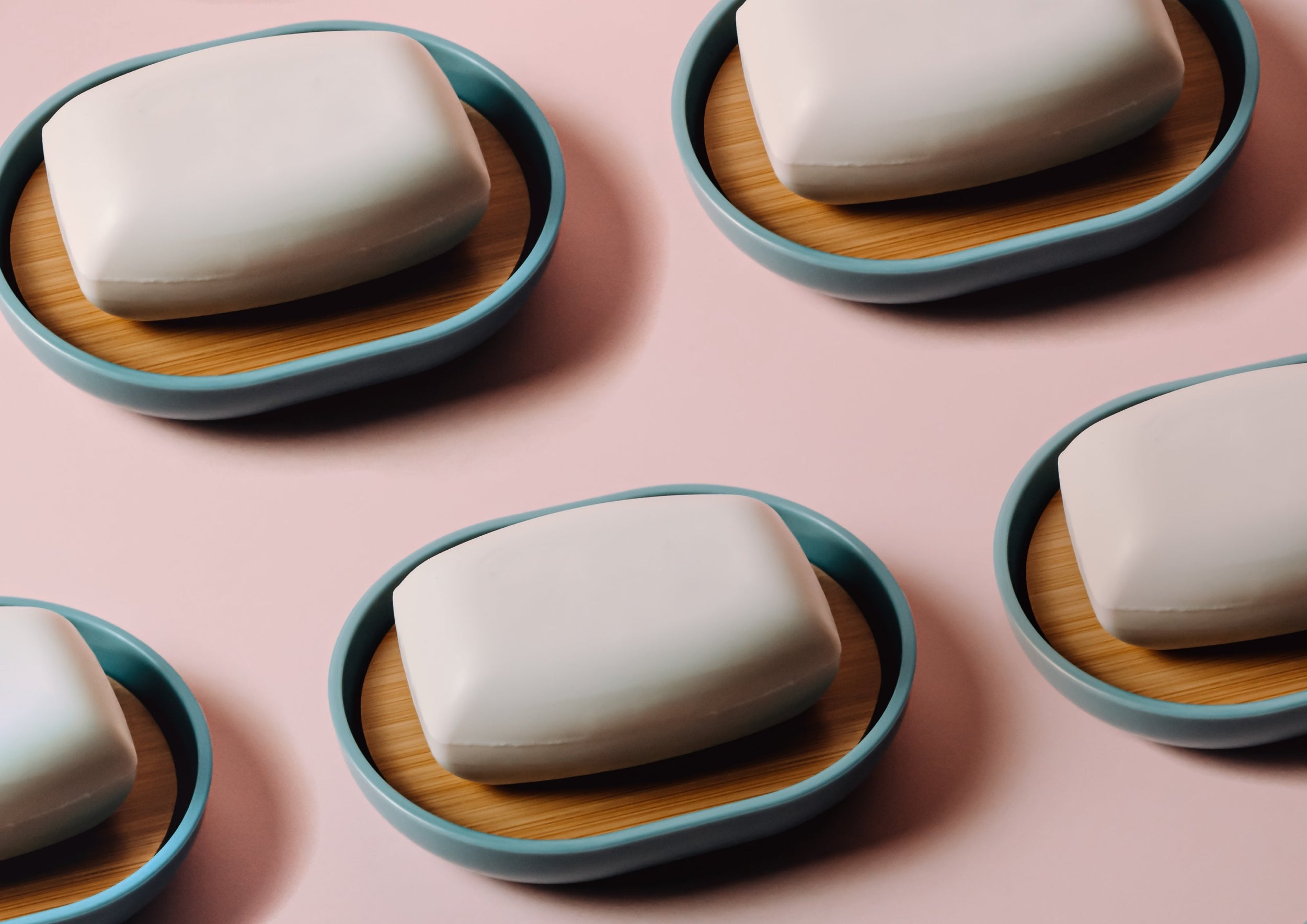 Several bars of soap are arranged on soap dishes on a pink background