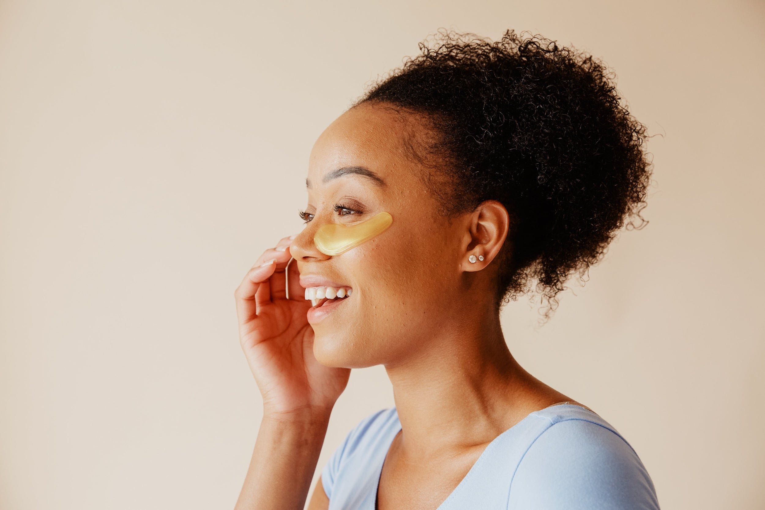 A smiling woman uses an eye mask skincare product