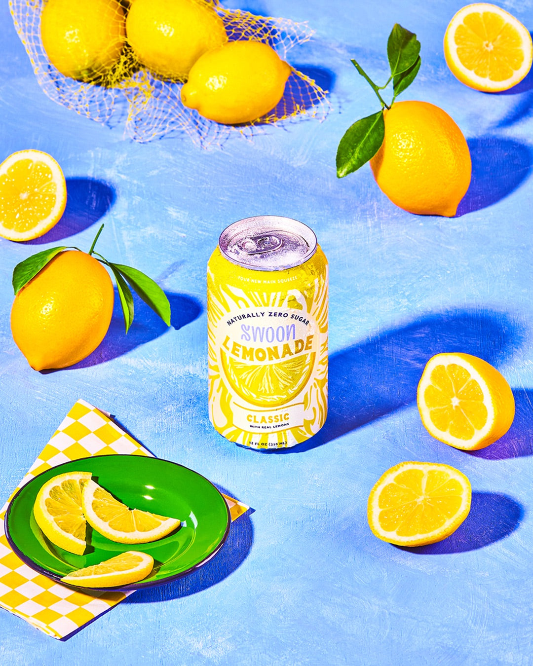 A can of classic Swoon lemonade against a blue background along with lemons displayed.