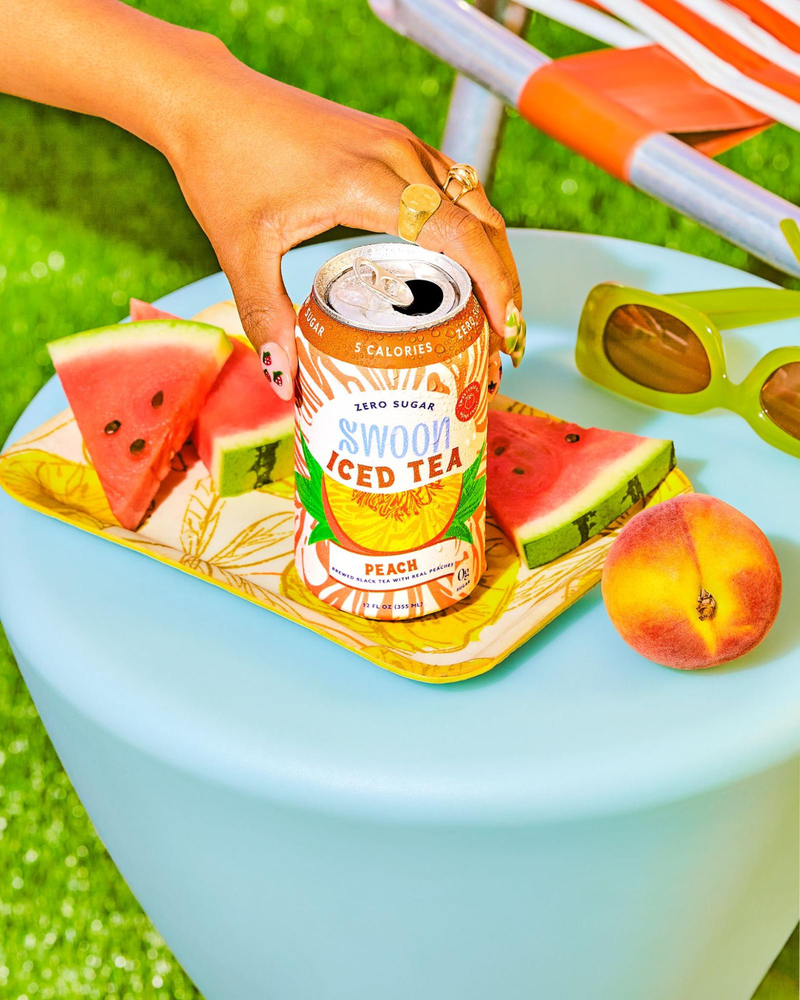 A peach-flavored iced tea by Swoon is placed on a blue table with fruits and sunglasses in the background.