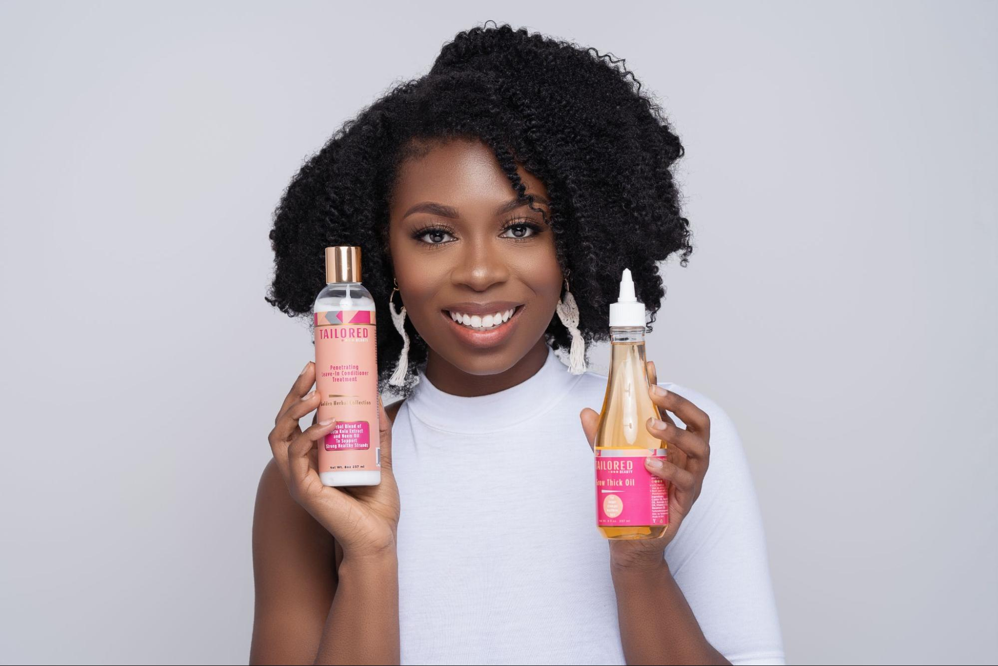 A model in a white outfit holding two of Tailored Beauty's products.