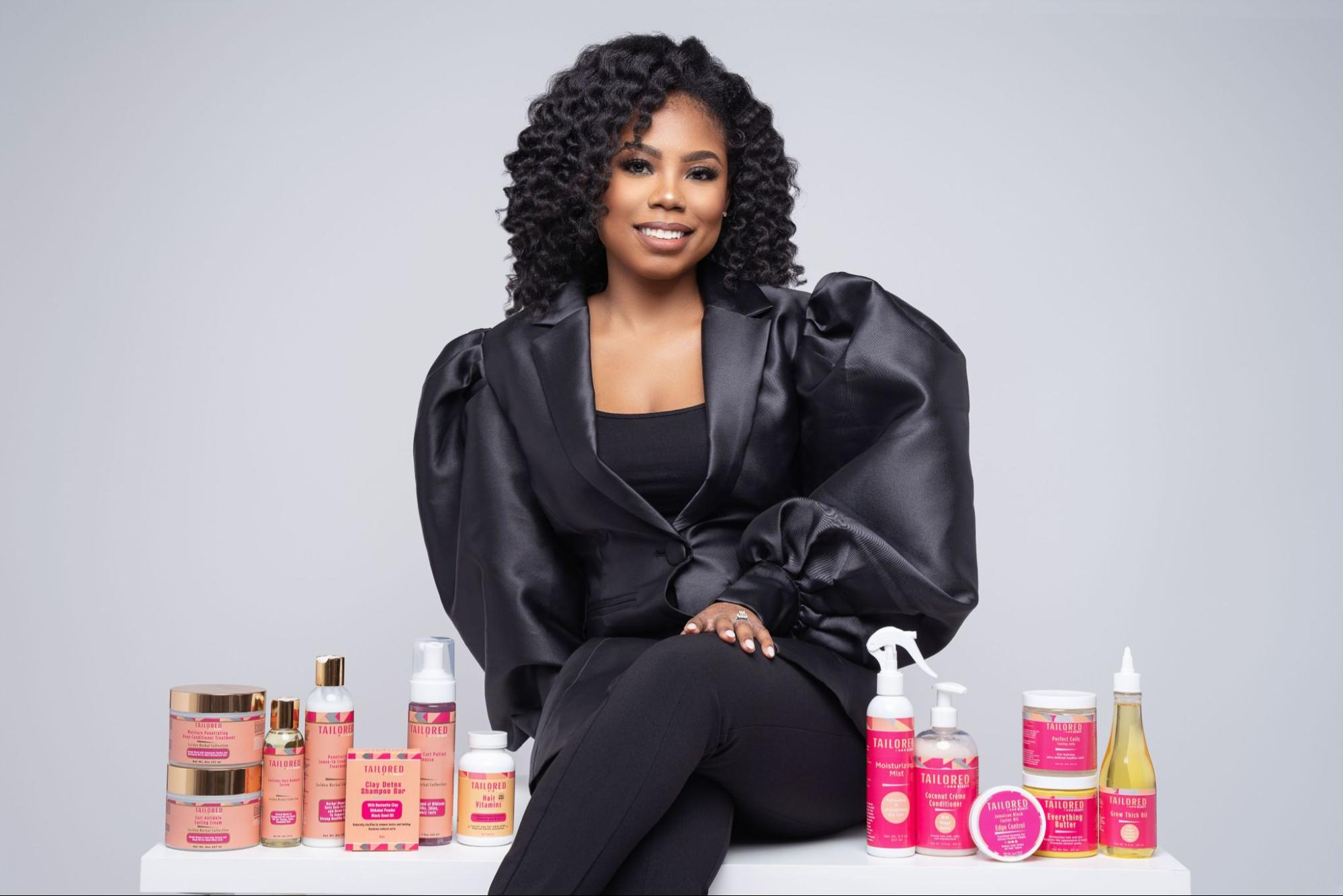 Kera James in an all black outfit along with some Tailored Beauty products.