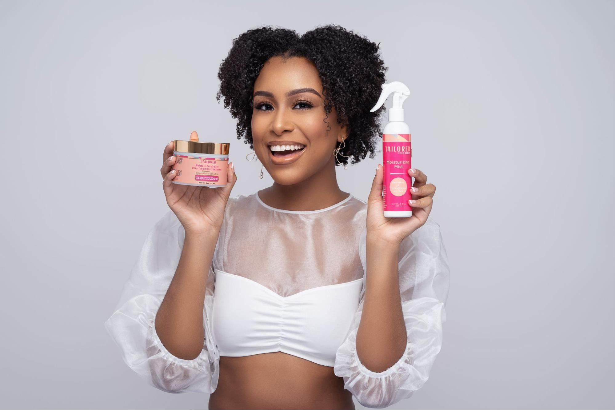 A model in a white outfit holding up two products from Tailored Beauty.