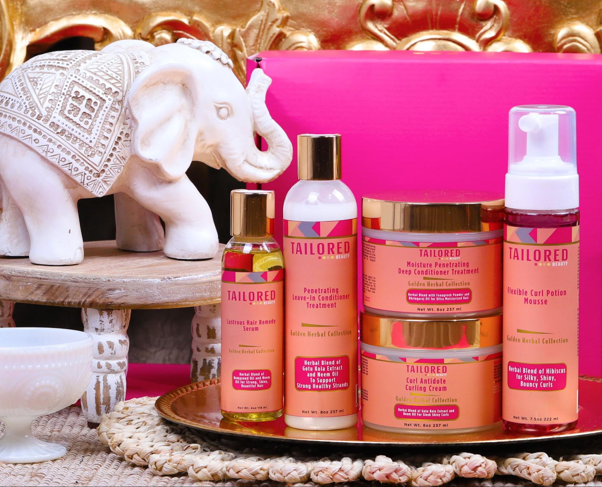 Tailored Beauty products backdropped by a pink background along with an elephant statue and a golden frame.