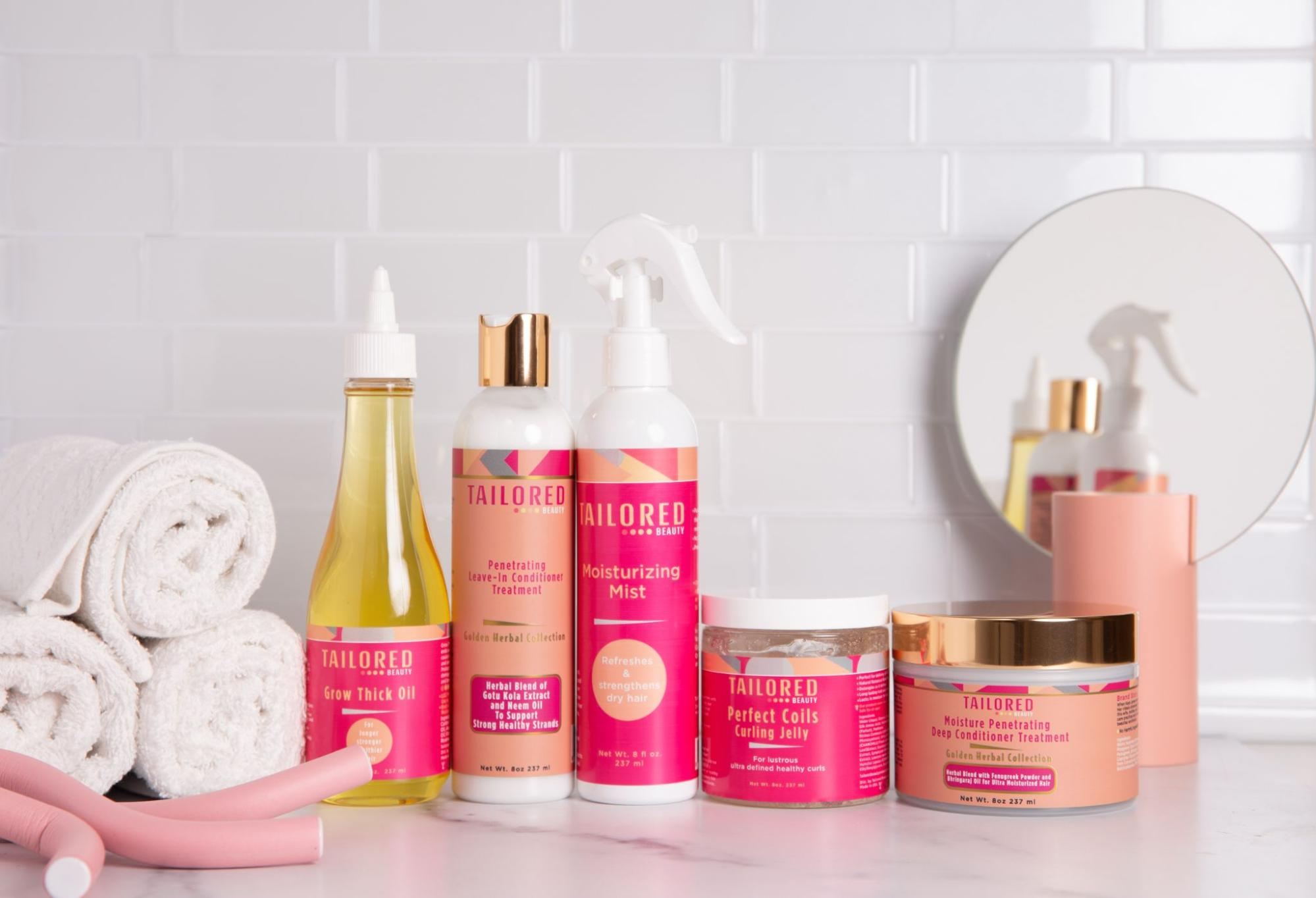 An array of Tailored Beauty products along with some towels, hair curlers, and a mirror.