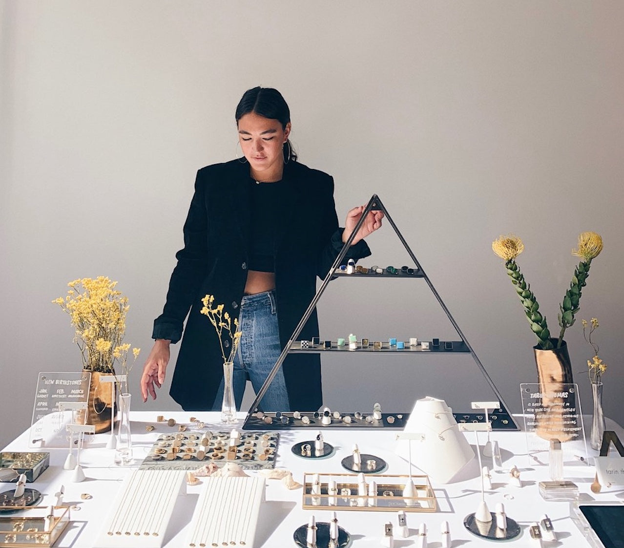 Artist Tarin Thomas standing behind a display table arranged with jewelry