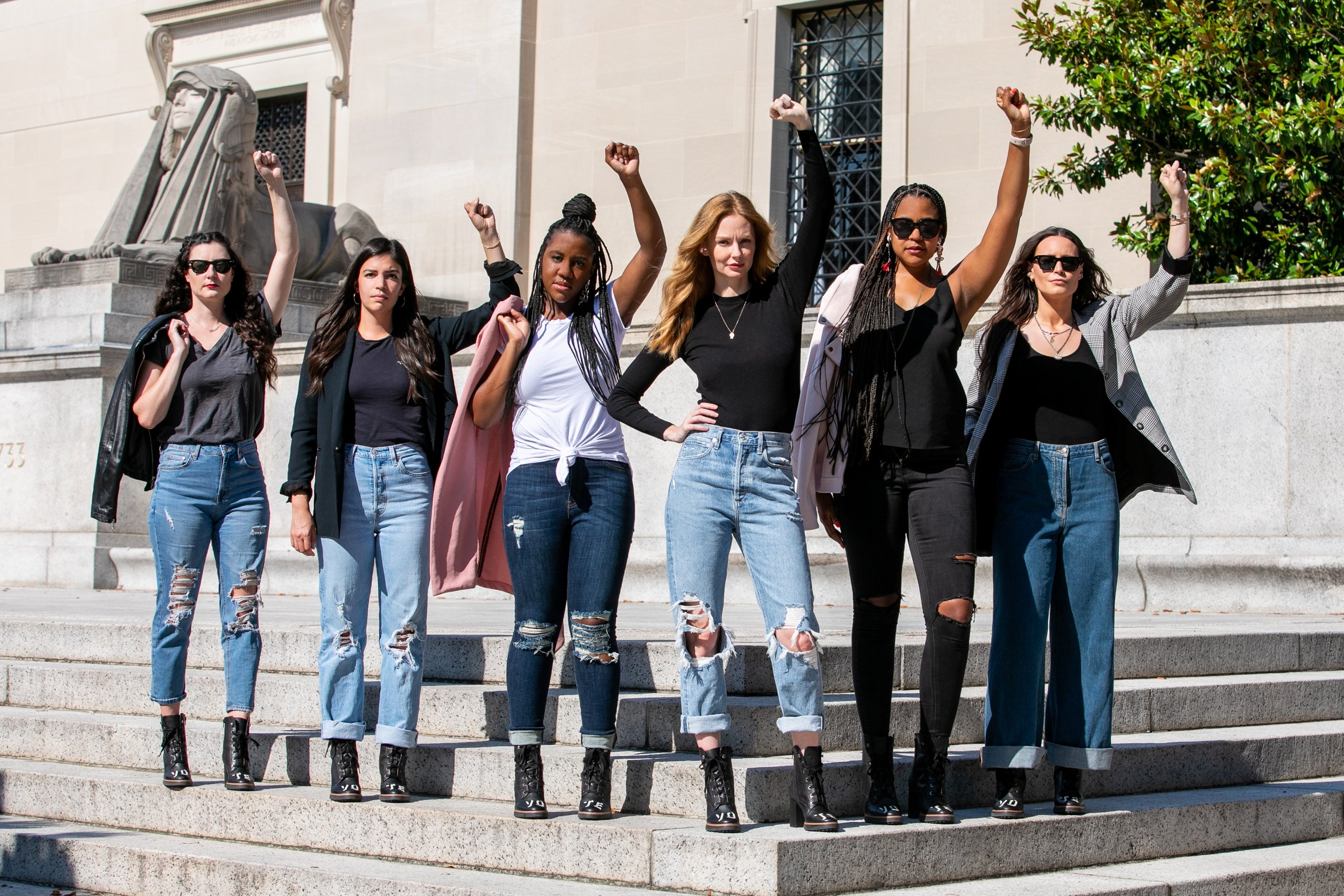 Six women stand on cement steps, all with fists raised in the air