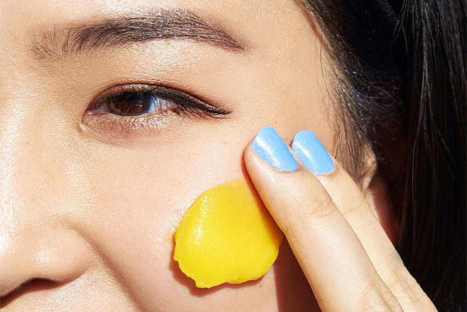 A woman rubs a yellow cleanser onto her face