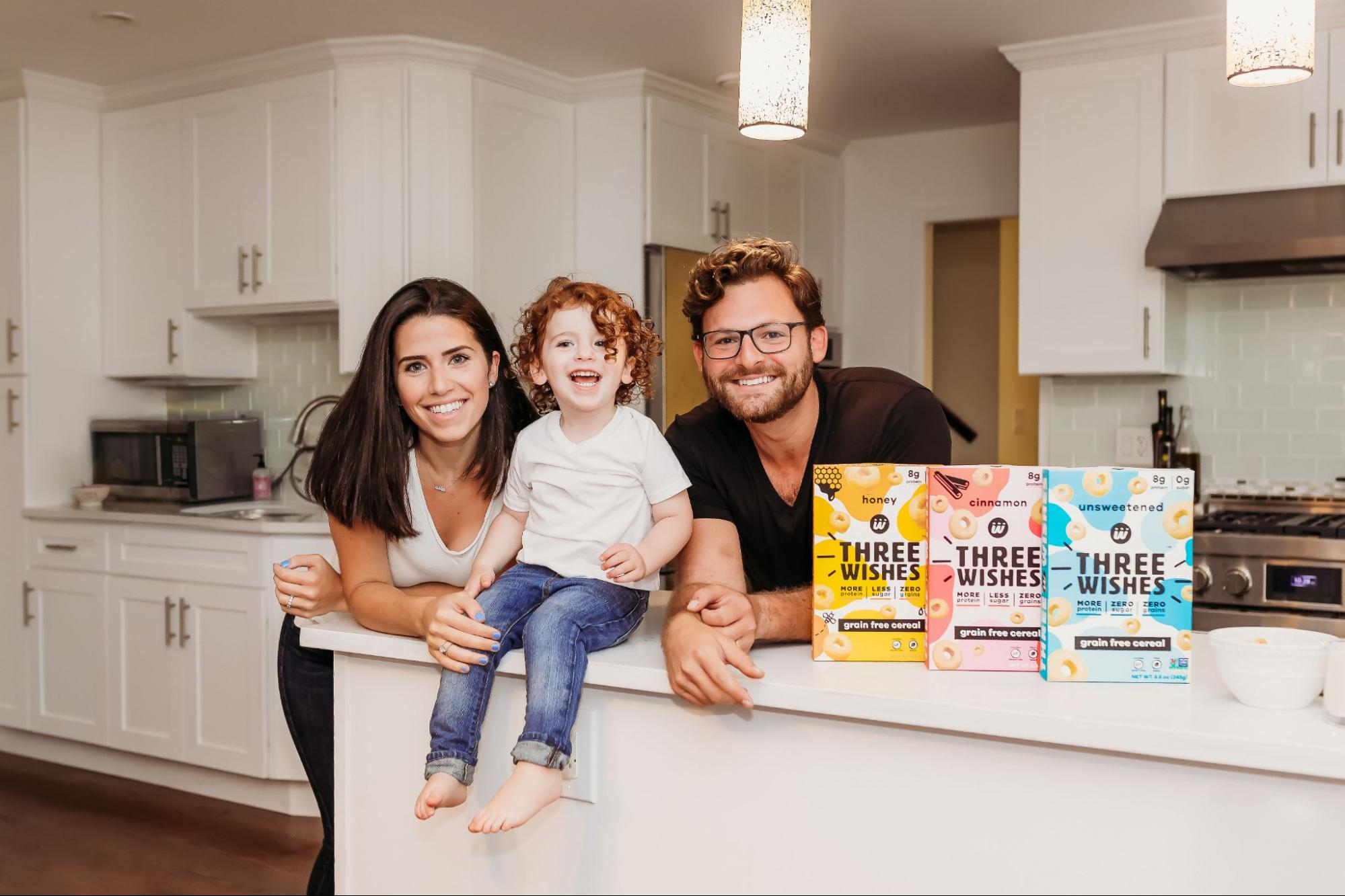 Margaret and Ian Wishingard along with their song Ellis in a kitchen setting with boxes of Three Wishes Cereal on the counter.
