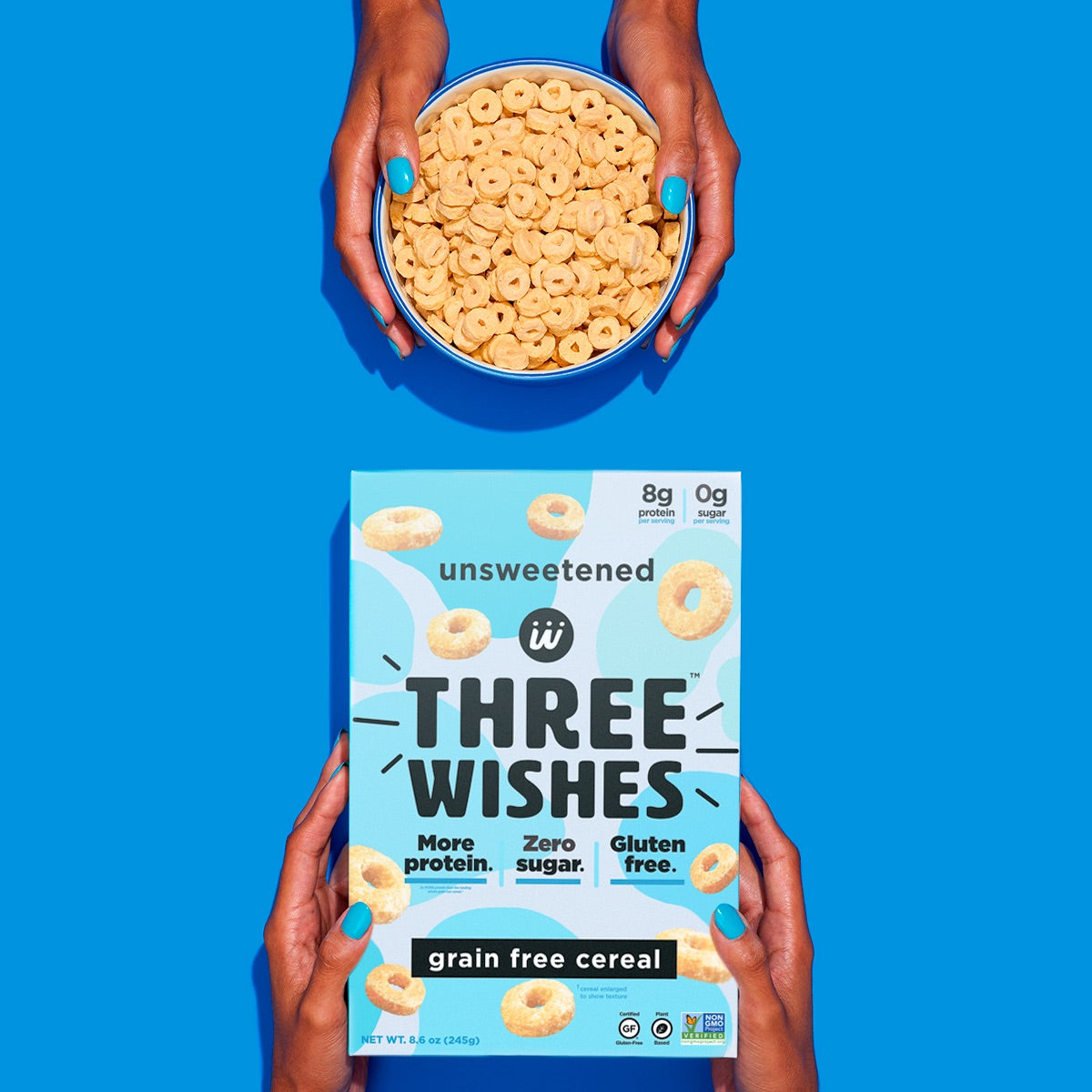 The unsweetened cereal by Three Wishes Creal held up by a pair of hands against a blue background.