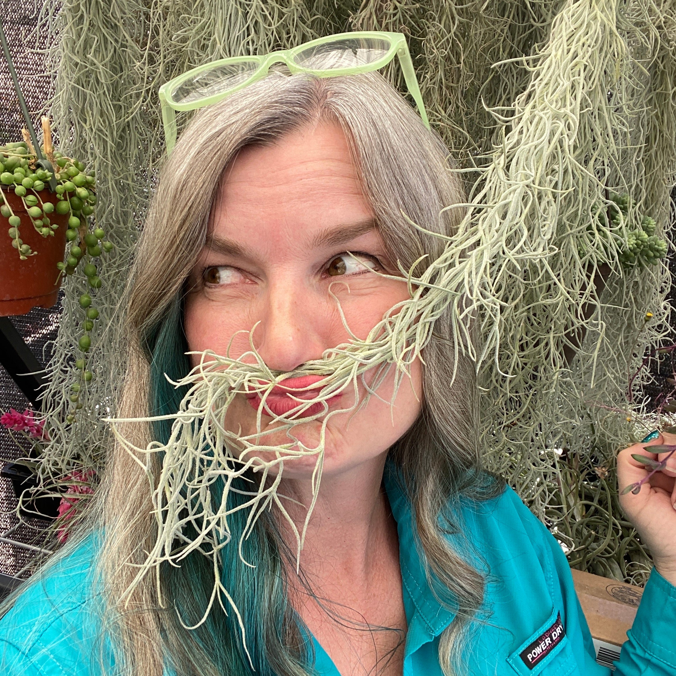 Portrait of Partly Sunny Projects' founder Sonja using a plant as a moustache