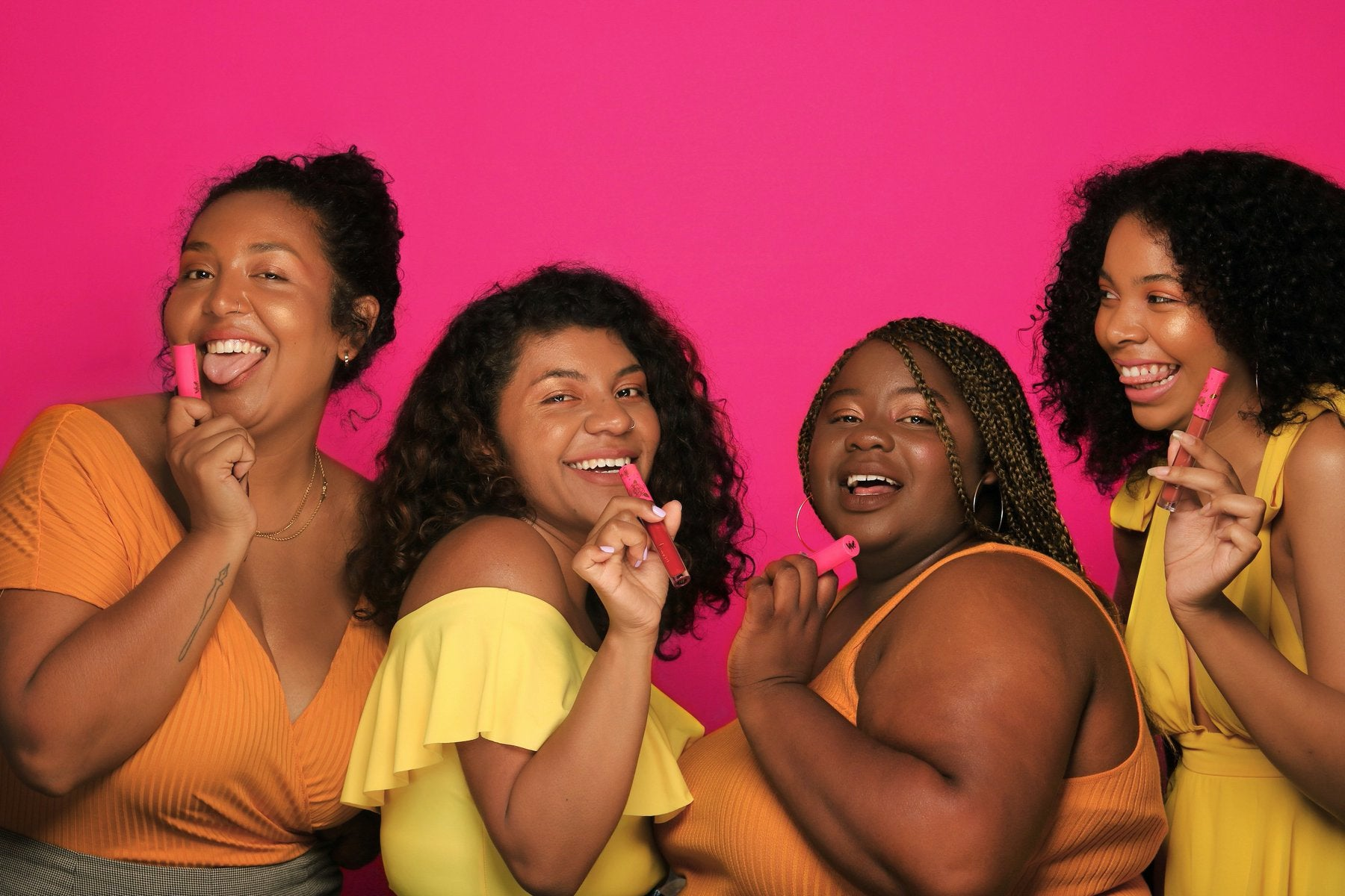 Four women wearing yellow hold lipsticks against a pink background