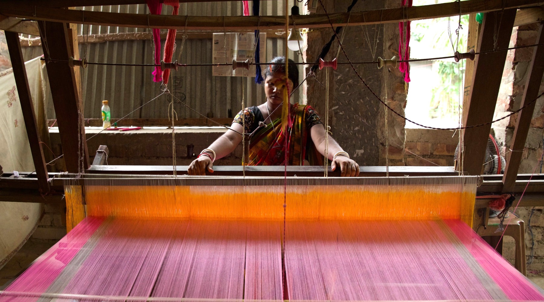 An artisan using a weaving machine to create a pink and gray fabric.