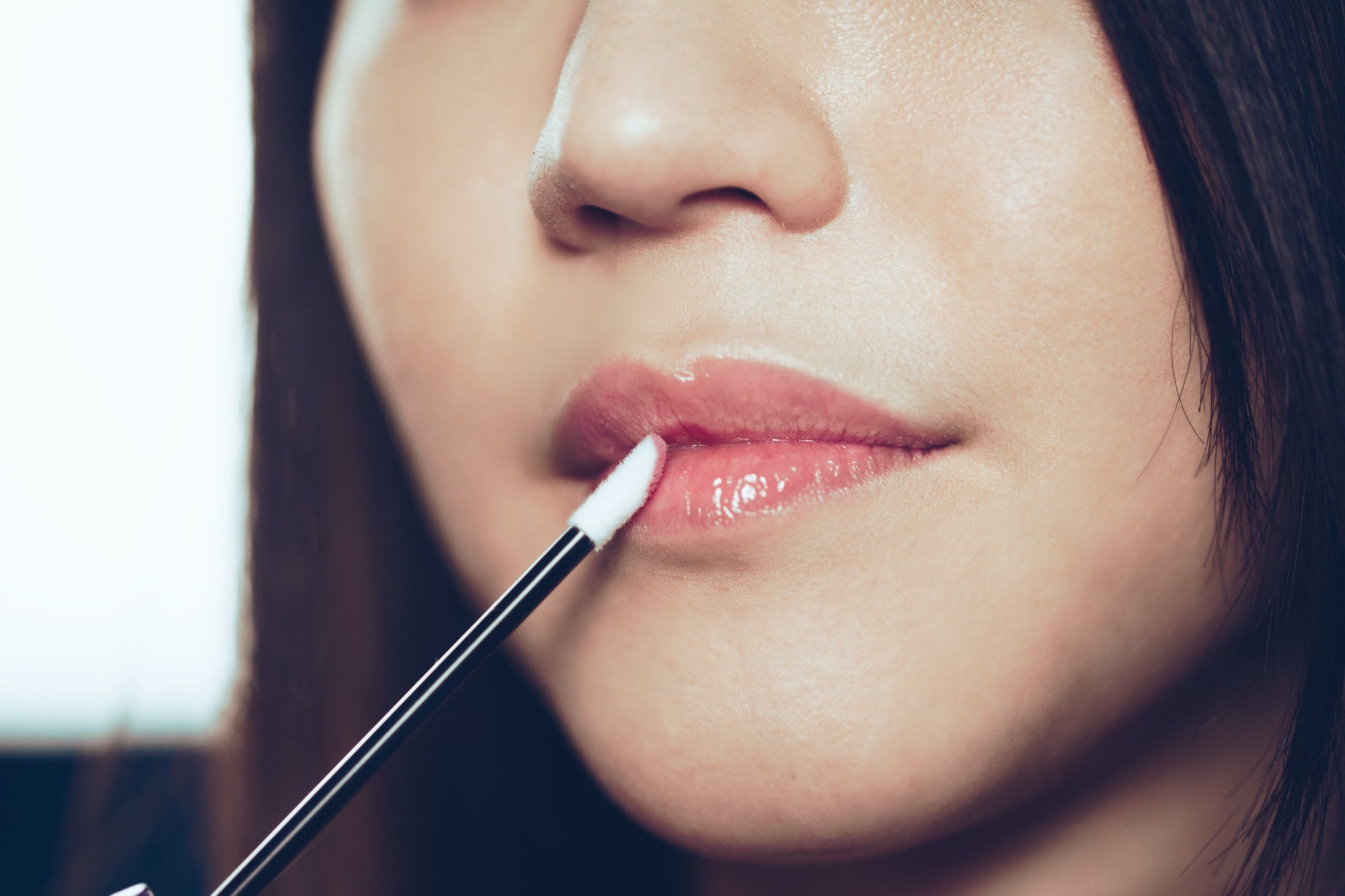 Close up of a woman applying clear lip gloss