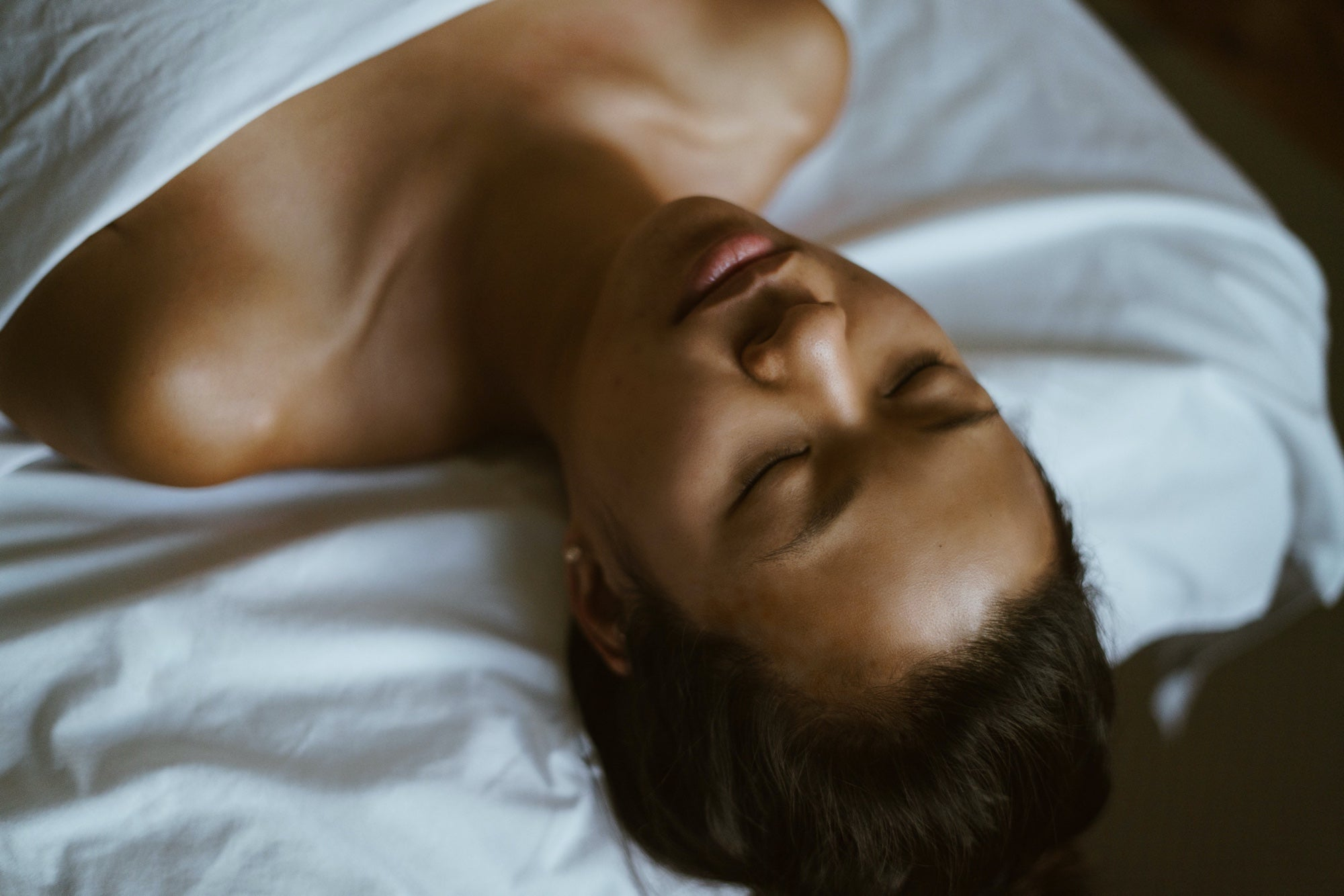 A woman lies on a massage table with her eyes closed