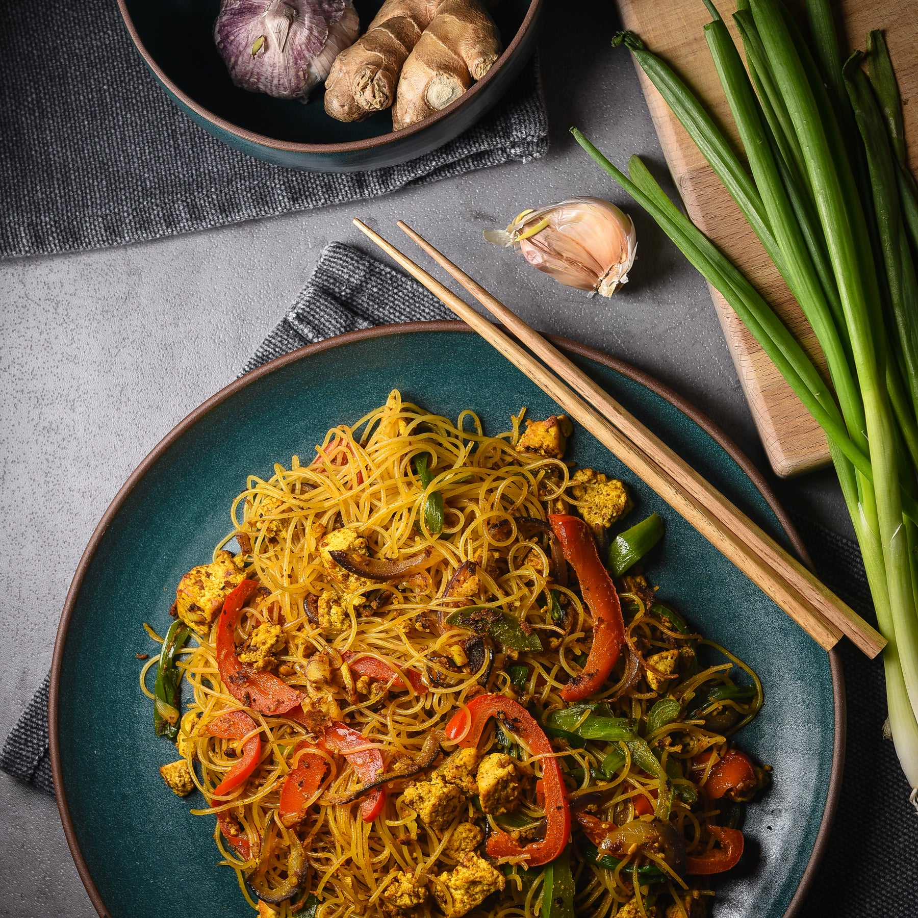 A plate of noodles with veggies surrounded by raw ingredients and chopsticks
