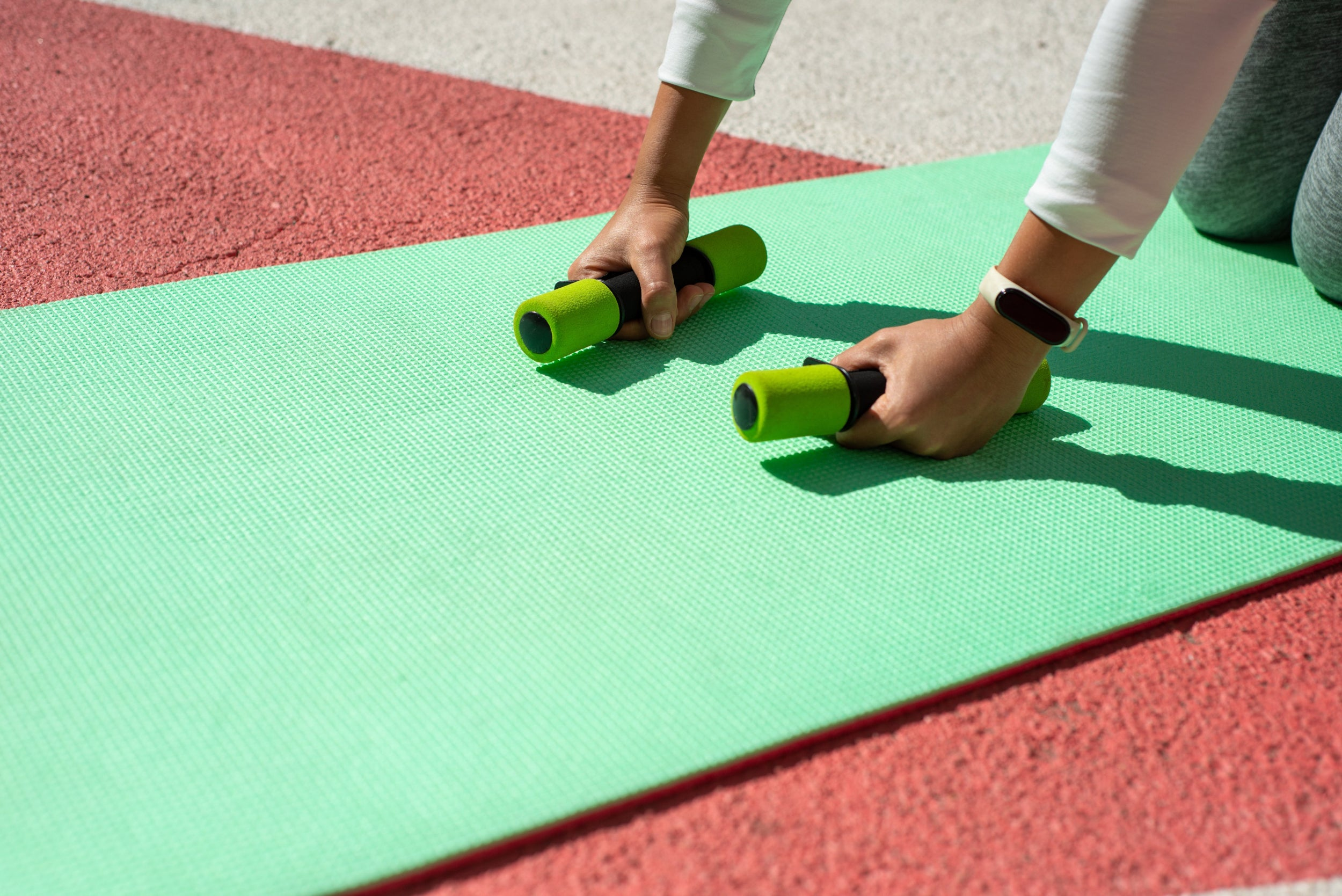 Two hands hold fitness weights on a green yoga mat