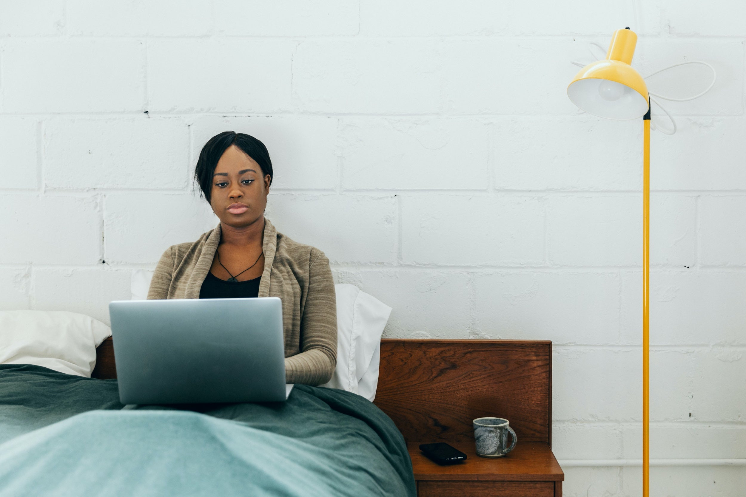 A woman works on a laptop in bed