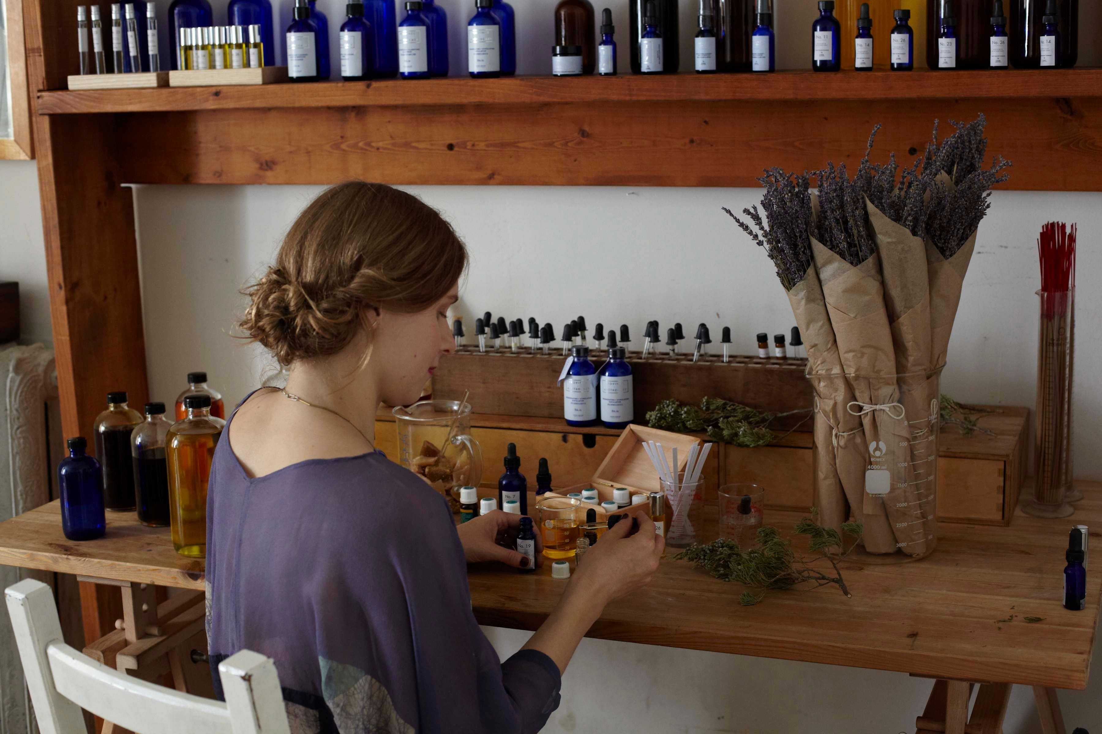 Julie Clarke at a desk preparing a product for her skincare line Province Apothecary.