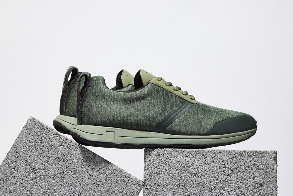 Green sneakers perched atop cinderblocks