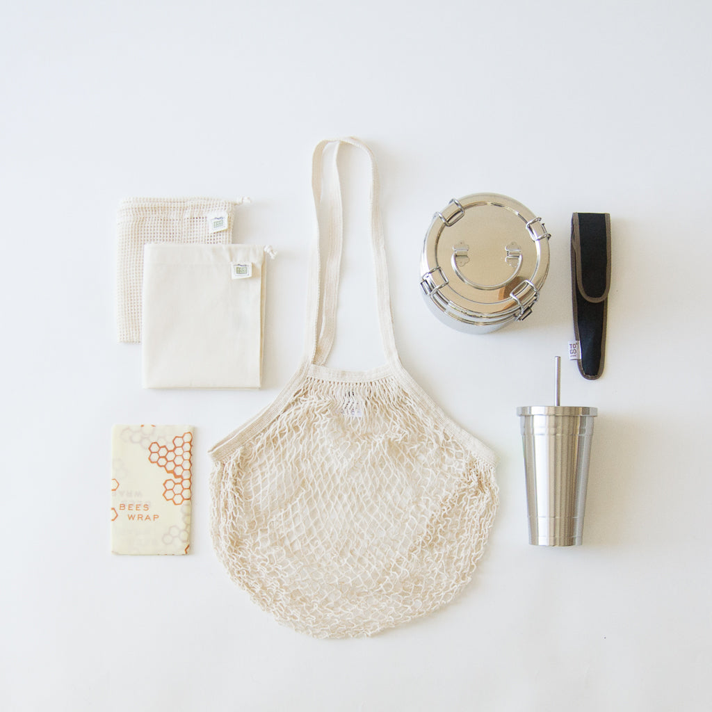 A zero-waste starter kit complete with French cotton net bag, cotton mesh produce bags, cotton muslin produce bags, beeswax wrappers, stainless steel lunchbox, stainless steel tumbler, and bamboo travel utensils.