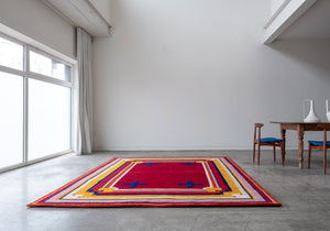 Mostly red rug with yellow and blue striped border and four blue crosses sitting on the floor next to a wood table with two chairs in a white room