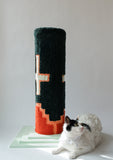 Green with white crosses and a red design along the bottom cat scratcher with a white cat sitting at the base