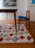 Light pink rug with red and light blue crosses sitting on a wood floor under a wood table with a wood chair