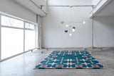 Green rug with a light pink hashtag design sitting on the floor with a light designed by Anony hanging above in a white room