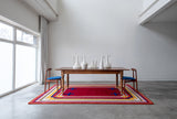 Mostly red rug with blue and yellow border and blue crosses under a wood table with two chairs in a white room