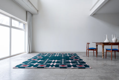 Green rug with a light pink hashtag design sitting on the floor next to a wood table in a white room