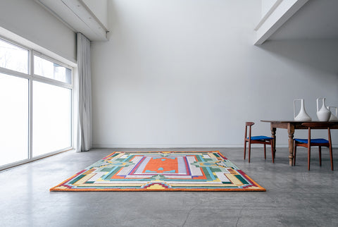 Orange green and yellow brightly designed rug sitting on the floor next to a wood table with two chairs in a white room