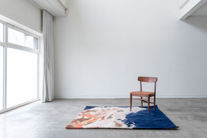 Mostly navy blue abstract painterly rug sitting on the floor under a wood chair in a white room