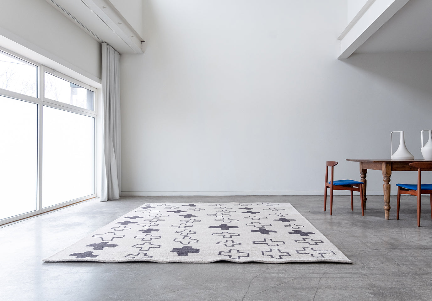 Cream and grey cross patterned rug sitting on the floor next to a wood table with two chairs in a white room