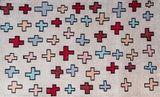 Full view of a light pink rug with red and light blue crosses