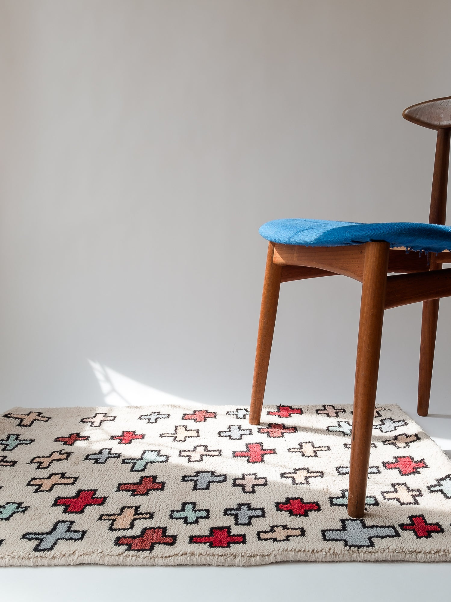Light pink rug with red and light blue crosses sitting on the floor under a wood chair with a blue seat in a white space