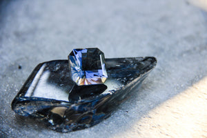 raw gemstone on piece of broken haitian glass