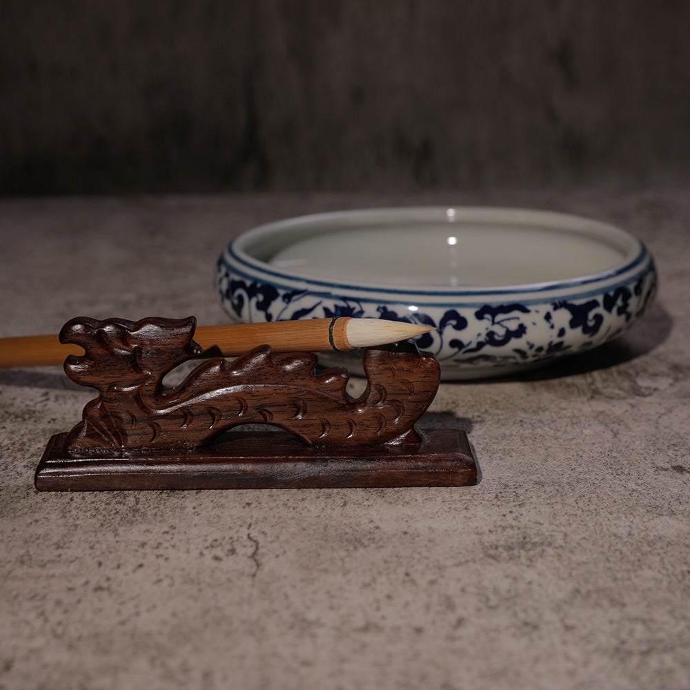 Ceramic Chinese water bowl with blue decorative pattern, Chinese fineline sumi brush resting on a wooden dragon brush rest