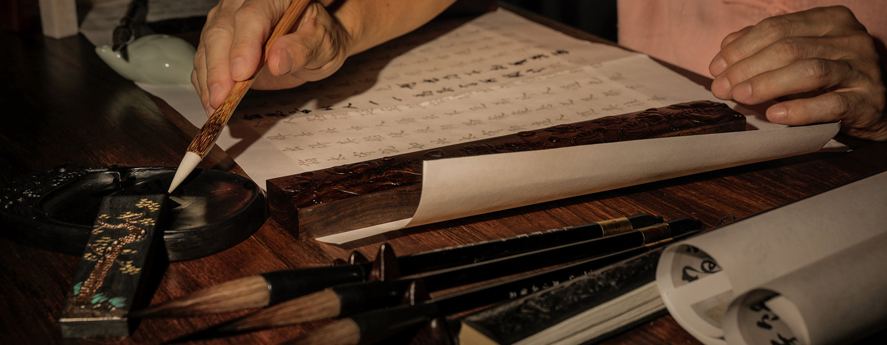 Chinese Calligraphy Artist practicing writing Chinese characters with a Chinese Brush and using the 4 Treasures of the Study