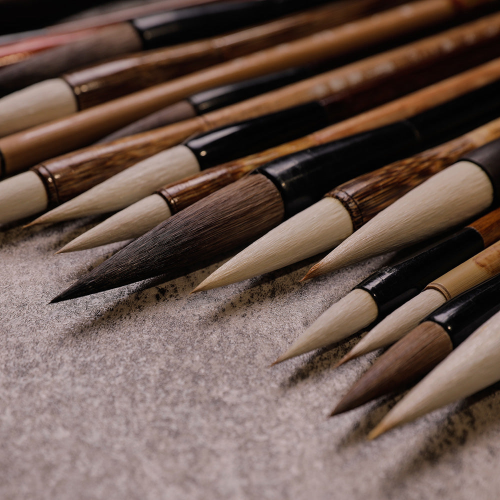 Closeup view of the tips of Chinese Calligraphy and Sumi Brushes with different tip sizes and beige bamboo handles and black wooden handles.