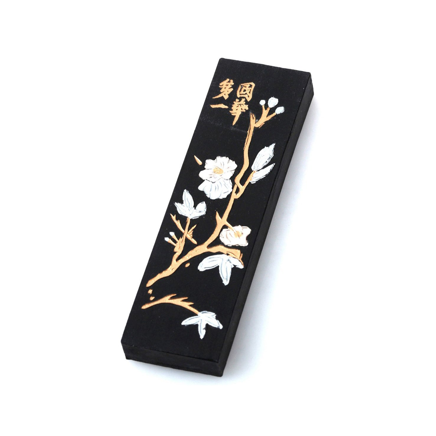 Black Japanes / Chinese ink stick for sumi and calligraphy, nicely decorated with white plum tree blossoms on golden branches and golden decorative Chinese lettering.
