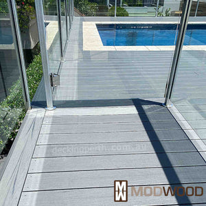 Modwood decking Magnetic Grey around a pool looking through the glass pool fence