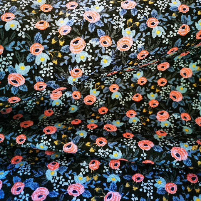 Black cotton covered with small flowers in pale pink, blues, white, green and yellow. Cotton and steel medium weight. 115cm wide.