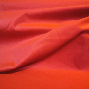 Pinwale cotton cord in orange red pimento with 4% elastane. 154cm wide.