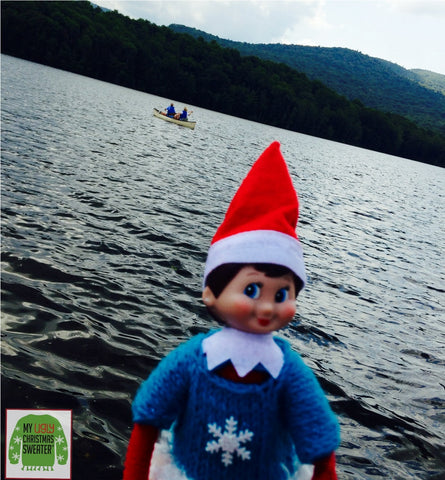 Elf on the shelf at the lake with a blue Christmas sweater. See more #elfontheshelf in #christmassweaters at www.myuglychristmassweater.com
