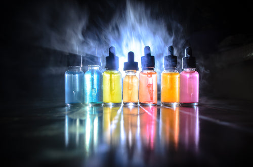 vape liquids and clouds on dark background
