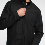 Zoomed in view of the front of a black zip up blouson jacket. Focused on the zipping up of the jacket.