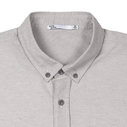 Flat lay focused on the collar of a heather grey, button up shirt. Can see the Tact & Stone neck label.