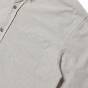 Zoomed in flat lay focusing on the left chest pocket of a heather grey button up shirt.
