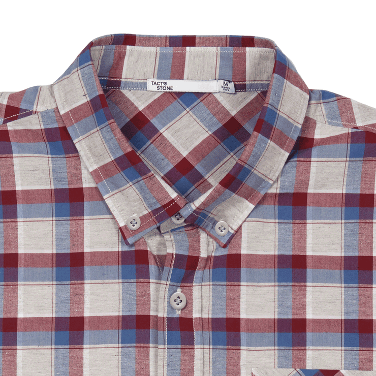Zoomed in flat lay of a plaid, button up shirt. Focused on the collar and top buttons of the shirt. Showing the Tact & Stone neck label.